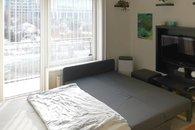 Pokoj s rozloženou postelí a sedací soupravou