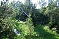Pohled na chatu od pozemku u potoka