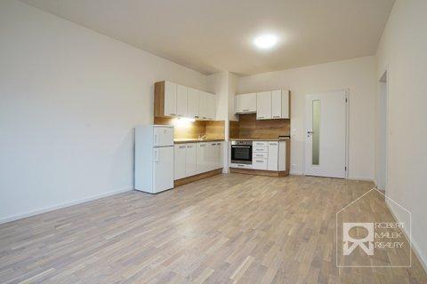 Obývací pokoj s kuchyňským koutem a vstupem na balkon
