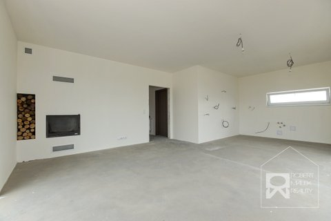 Obývací pokoj s krbem a kuchyňským koutem